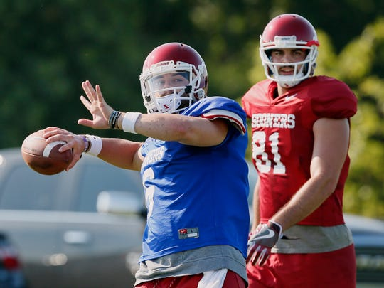 Oklahoma quarterback Baker Mayfield, left, throws in