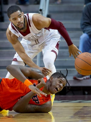 New Mexico State's Shunn Buchanan and UTEP's Tirus Smith fight for the loose ball during first half action Saturday night at the Pan American Center.