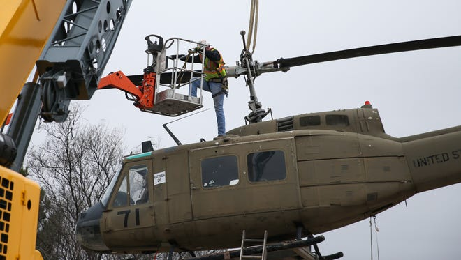 Goins Crane Service crew attach cables to the helicopter to lift it off its perch Friday, Jan. 13, 2017, at the Vietnam War Memorial.