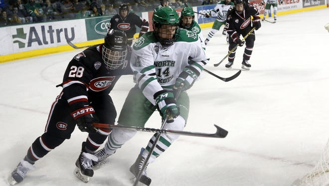 North Dakota's Austin Poganski (14) tries to win a puck battle against St. Cloud State's Andrew Prochno. Poganski, a Cathedral High School graduate, will play in his last regular season series this weekend at the Herb Brooks National Hockey Center.