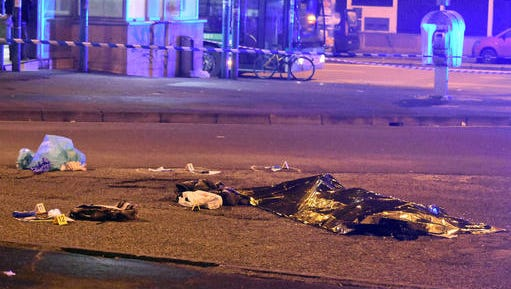 """A thermical blanket covers a body moments after a shootout between police and a man near a train station in Milan's Sesto San Giovanni neighborhood, Italy, early Friday, Dec. 23, 2016. Italy's interior minister Marco Minniti says the man killed in an early-hours shootout in Milan is """"without a shadow of doubt"""" the Berlin Christmas market attacker Anis Amri."""