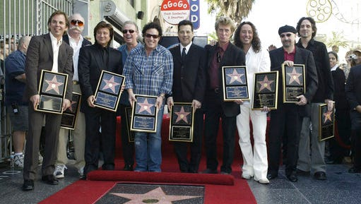 FILE - In this Jan. 21, 2005, file photo, members of the band Journey pose after receiving a star on the Hollywood Walk of Fame in Los Angeles. Keyboardist Jonathan Cain told the Dayton Daily News for a story published online on March 30, 2017, that former singer Steve Perry will be in attendance when the band is inducted into the Rock and Roll Hall of Fame on April 7, 2017.