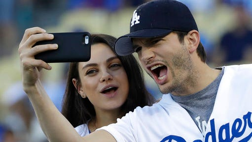 FILE- In this Oct. 19, 2016, file photo, Ashton Kutcher and wife Mila Kunis take a selfie before Game 4 of the National League baseball championship series between the Chicago Cubs and the Los Angeles Dodgers in Los Angeles. Kutcher offered emotional praise for his wife Mila Kunis, his twin brother and the rest of his family in accepting an award for character in his native Iowa on April 9, 2017.