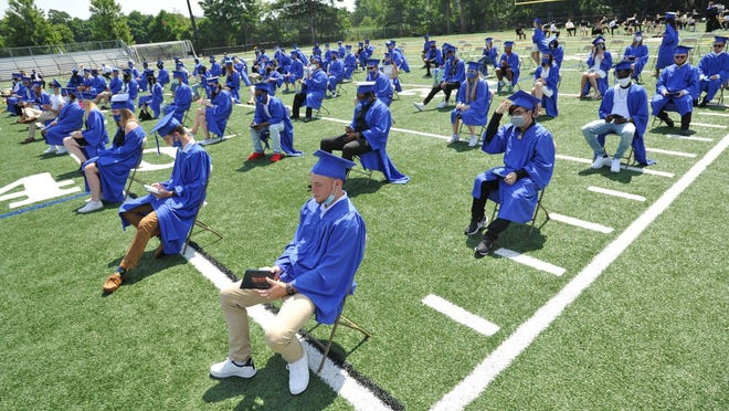 Graduating seniors are socially distanced during the Quincy High School graduation at Adams Field in Quincy, Saturday, July 25, 2020. Tom Gorman/For The Patriot Ledger