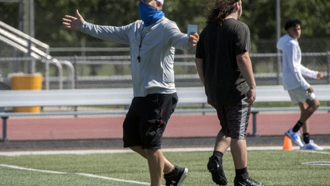(7/7/20) John Ward, head varsity football coach with Chavez High runs player though a drill during a summer conditioning camp at the school in Stockton.