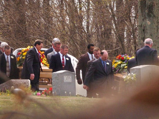 Pallbearers carry the caskets of Brad and Tanya Taylor