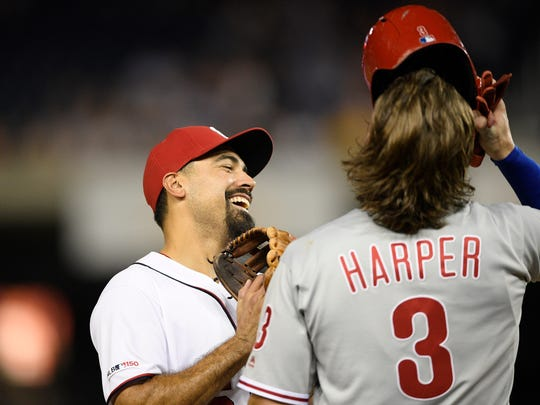 Washington Nationals third baseman Anthony Rendon, left, laughs next to Philadelphia Phillies' Bryce Harper (3) as they stand at third during the sixth inning of a baseball game Monday.
