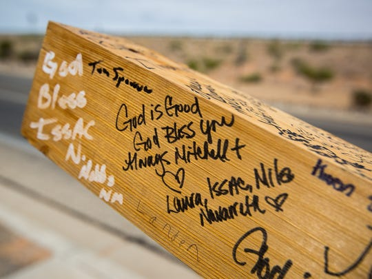 Mitchell Manning's Western red-cedar cross is covered with well wishes from people he's encountered on his walking trip from Florida to California, Tuesday, August 9, 2016.