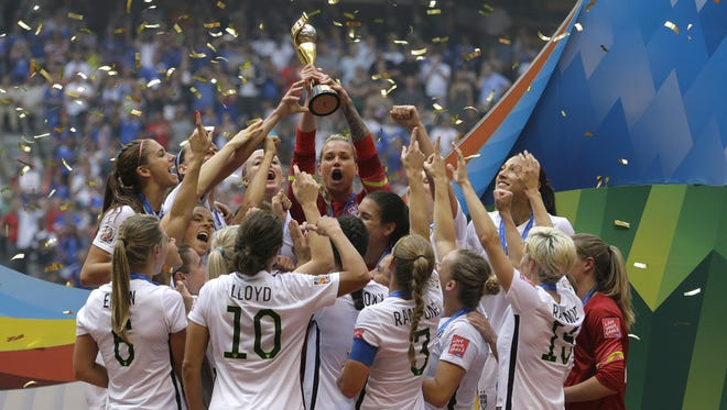 Satellite's Ashlyn Harris holds up the FIFA Women's World Cup trophy around her United States Women's National Team teammates after they beat Japan 5-2 in the championship Sunday.
