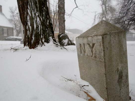 A New York City mile marker partially buried in the