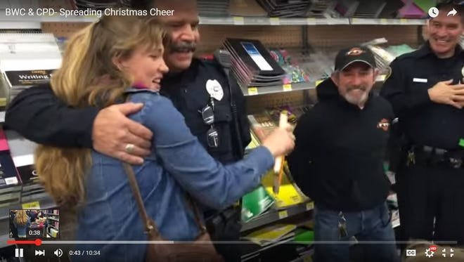 Police and BWC members get a hug in exchange for their gift to a shopper Friday.