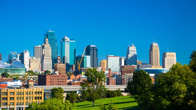 Downtown Kansas City skyline with Penn Valley Park in the foreground and a vivid blue sky in the background.