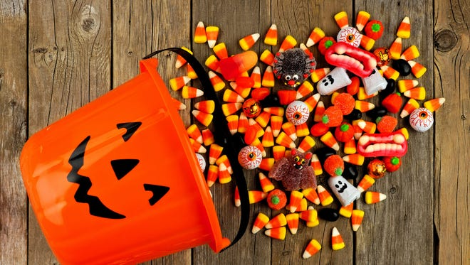 A Halloween trick-or-treating pail is shown with candy spilling out.