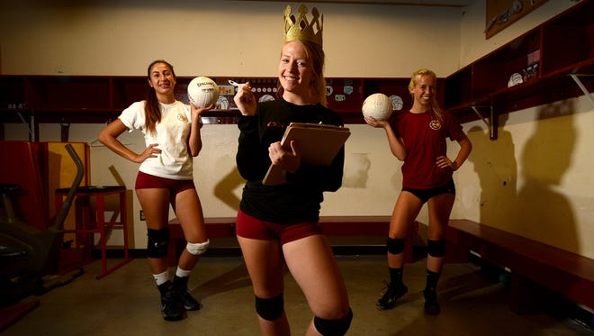 """Jazmine Toledo (left),  middle blocker, Shea McKeown (right), outside hitter, and the rest of the Oxnard girls volleyball team  call Devon Glinski (center) """"mom"""" because of how she looks after the players and makes sure everyone is doing what they are supposed to be doing."""