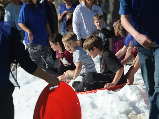 Kids ride saucers down a snowy slope at the 8th Annual Coats for Casa Pacifica at Three Springs Park on Saturday afternoon.