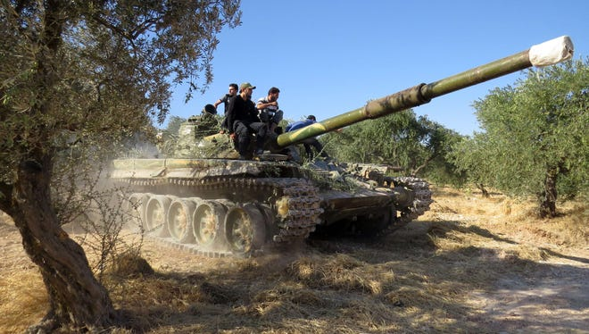 Rebel fighters sit on top of a tank that formally belonged to the Syrian army during a battle with government forces in the rebel-held northwestern Syrian province of Idlib on Monday.
