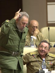FILE - In this June 26, 2002 file photo, Cuba's leader Fidel Castro, left, votes in favor of the modification on the Cuban Constitution, as his brother, Defense Minister Raul Castro, looks on during an extraordinary National Assembly session in the Convention Palace in Havana, Cuba. Former President Fidel Castro, who led a rebel army to improbable victory in Cuba, embraced Soviet-style communism and defied the power of 10 U.S. presidents during his half century rule, has died at age 90. The bearded revolutionary, who survived a crippling U.S. trade embargo as well as dozens, possibly hundreds, of assassination plots, died eight years after ill health forced him to formally hand power over to his younger brother Raul, who announced his death late Friday, Nov. 25, 2016, on state television. (AP Photo/Cristobal Herrera, File)