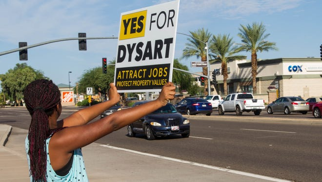 Jayde Williams, 10, waves at cars on Bell Road in Surprise on Sept. 12, 2015. The Dysart Unified School District is trying to generate support for an upcoming override, which if lost, will result in a $6 million cut.