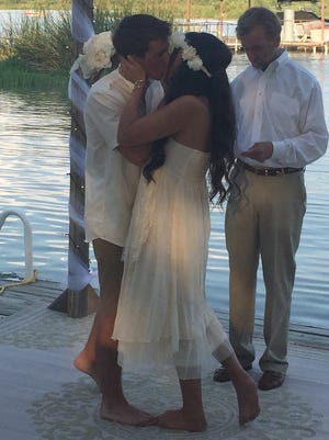Kaleb Pierce and Kameron Wike kiss as they tie the knot on a dock at Lake Nasworthy.