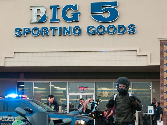 """Steven Gerace walks to his motorcycle Monday as a man is tended to by first responders in the background. The man was hit in the head by a portion of the Big 5 Sporting Goods sign. While waiting for first responders to arrive, Gerace said, """"I had to hold a flap of his skin on to his head."""""""