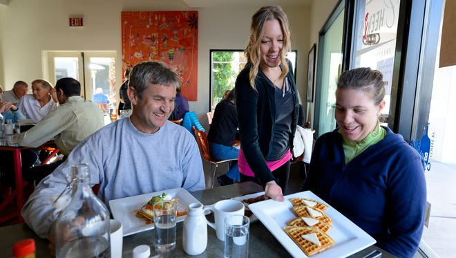 Bryanna Evaro serves breakfast to customers Paul and Lindsay Kaufman at Cheeky's, a popular downtown restaurant in Palm Springs.