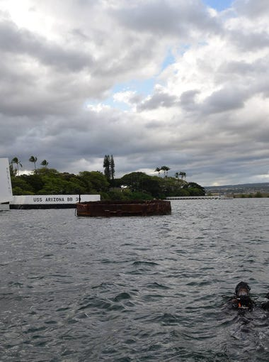 Divers hold aloft an urn with the remains of Raymond Haerry, who was a crewman on the USS Arizona when it was attacked at Pearl Harbor. The divers were taking the remains beneath the Arizona memorial to inter them in the wreckage of the battleship.