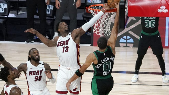 Heat center Bam Adebayo (middle) blocks the potential game-tying dunk by Celtics forward Jayson Tatum (foreground) as Jimmy Butler (bottom left) and Jae Crowder (second left) in the closing seconds of overtime in Game 1 of the Eastern Conference Finals Tuesday night in Lake Buena Vista, Fla.