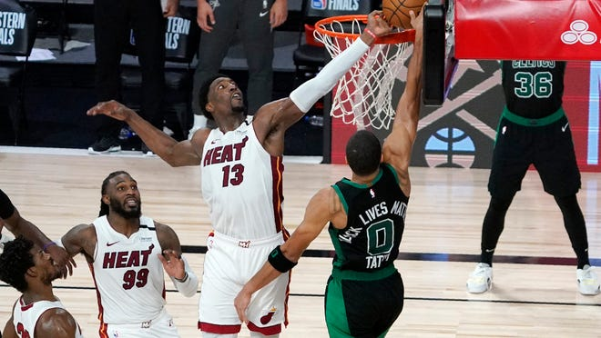 Miami Heat's Jimmy Butler, bottom left, and Jae Crowder (99) look on as Bam Adebayo (13) blocks a shot attempt by Boston Celtics' Jayson Tatum (0) in the closing seconds of overtime of an NBA conference final playoff basketball game, Tuesday, Sept. 15, 2020, in Lake Buena Vista, Fla.