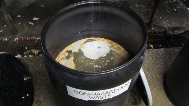 """PHOTO 2: Leftover chemicals drain into a plastic barrel at Indy Drum. State and federal workplace safety inspectors toured the plant in 2010 when this photo was taken. Federal inspectors """"observed multiple totes"""" with as much as 3 inches of liquid. Inspectors found that a """"large percentage"""" of the chemicals in the plant were toxic liquids such as hydrofluoric and hydrochloric acids, sodium hydroxide, ammonia, diacetyl, acetone, benzene, nickel and formaldehyde."""