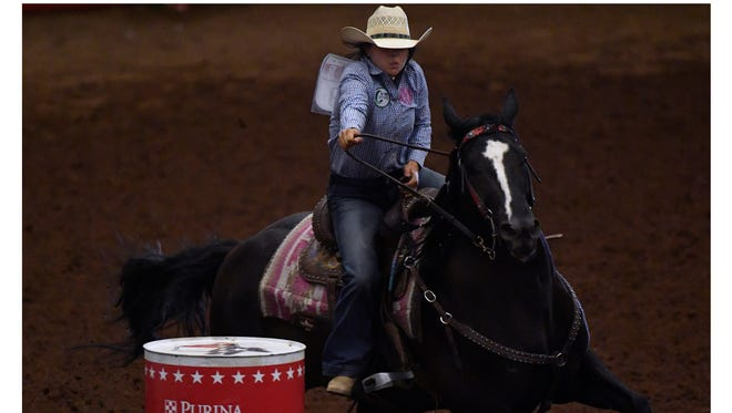 Madison Bean of Clint urges her horse to run faster during barrel racing at last year's Texas High School Rodeo Association Finals at the Taylor County Coliseum.