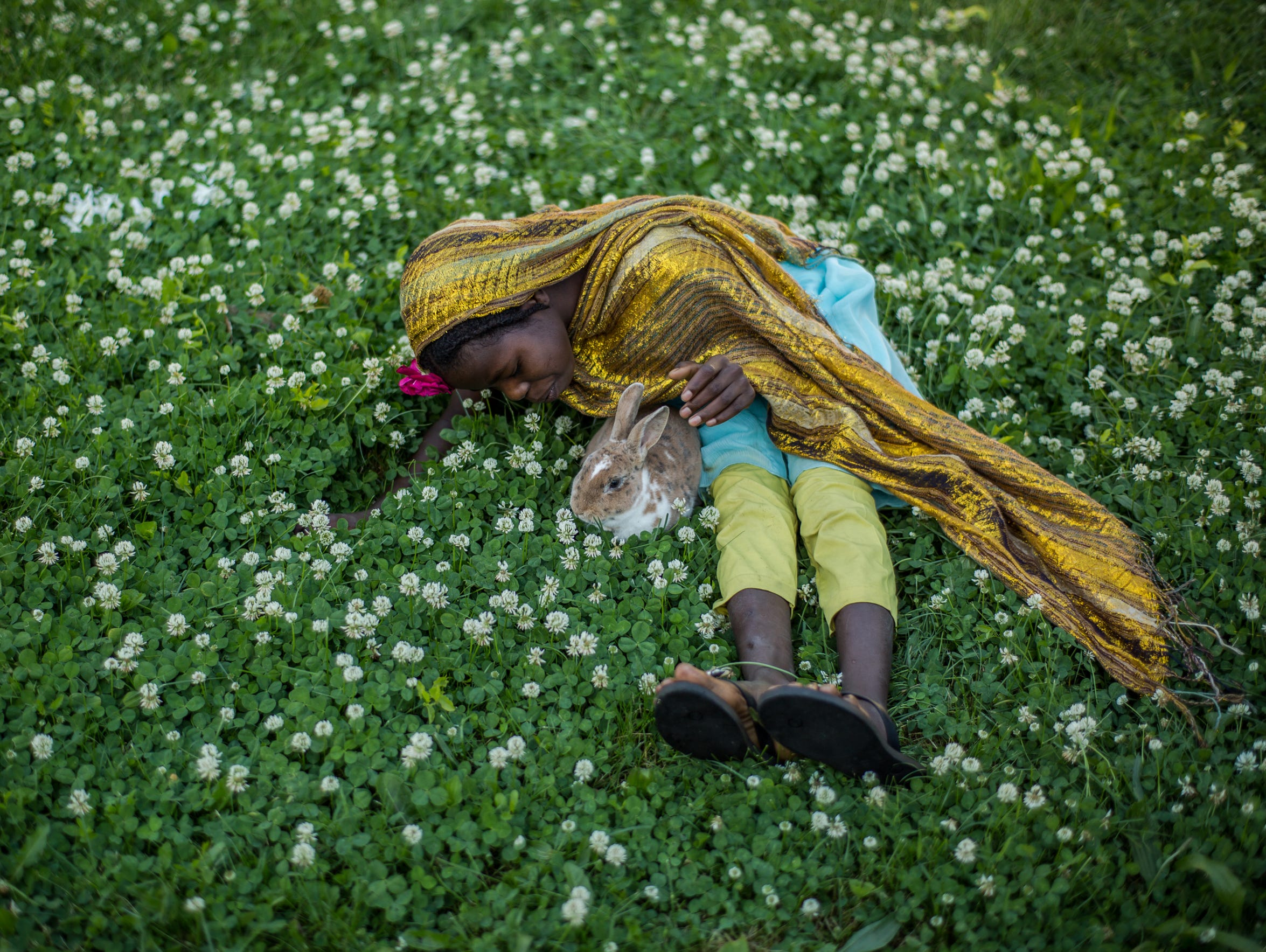 Guisma Yacoub, 12, of Detroit, plays with a rabbit,