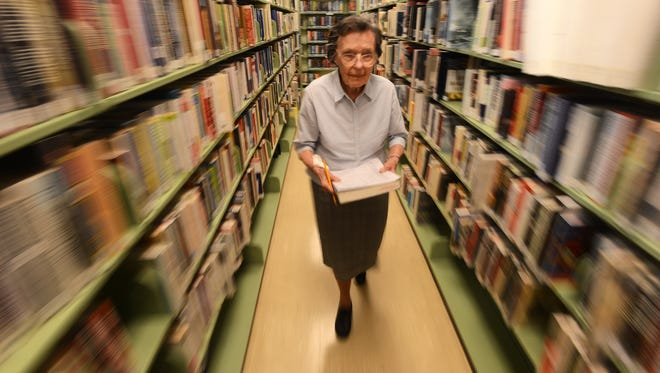 Long-time Eastern Shore Public Library volunteer Grace Murphy looks over her list as she tracks down requested books for library patrons on Wednesday, June 3, 2015. Murphy, 92, volunteers at the library twice a week and has been volunteering for the non-profit for more than 60 years.