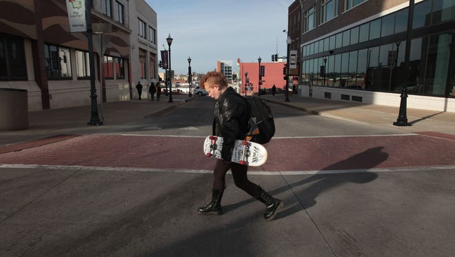 Lyzz Buford walks across the square in downtown Springfield wearing her boyfriend's jacket and carrying his skateboard on Jan. 30. She was heading toward the downtown bus transfer station to go job-hunting.