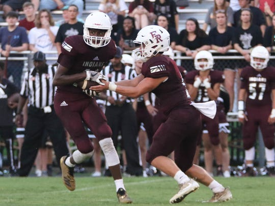 East Robertson quarterback Cameron Swift hands the ball to Taylor Groves.
