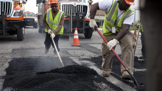 Jason Small, left, and Dwayne Toland spread and level hot asphalt on Aug. 26 at the intersection of Conant and Norwalk streets in Hamtramck.