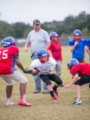 Coach Donnie Roper, top, watches as his players run a drill during Pace Athletic and Recreation Association football's 11-and-under Blue Midgets team practices in an outfield of a baseball field at the Santa Rosa Sports Plex in Pace on Monday, October 2, 2017.