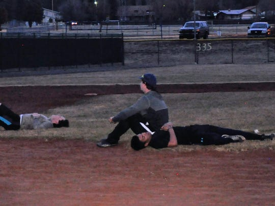 Ruidoso baseball players collapse on the field after a chilly practice Monday.