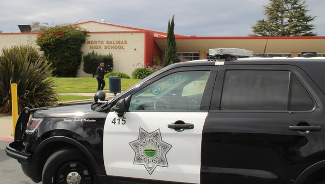 A Salinas police officer walks into North Salinas High School Monday afternoon to investigate a graffiti threat that a shooting would take place that afternoon.