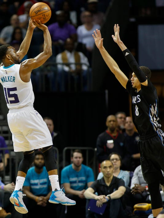 Charlotte Hornets guard Kemba Walker,  left, shoots over Minnesota Timberwolves guard Zach LaVine in the second half of an NBA basketball game in Charlotte, N.C., Monday, March 7, 2016. Charlotte won 108-103.  (AP Photo/Nell Redmond)