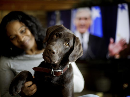 Alicia Barnett sits with her Chocolate Labrador Retriever