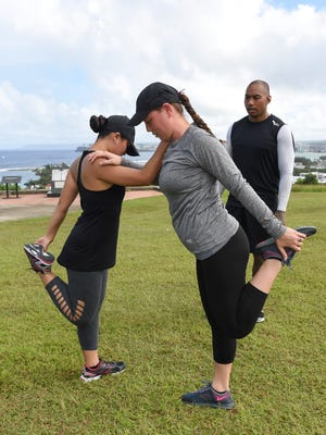 """Fitness professional Ray Chargualaf observes Kristina Cruz, left, and Derene Faculo, right, as they perform quad stretches before their """"Find Your Swole-Mate"""" exercises at Fort Santa Agueda in Hagatna on Nov. 19, 2016."""