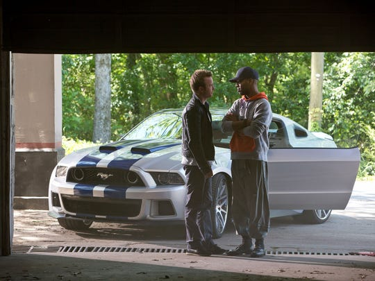 Aaron Paul, left, and Scott Mescudi with a Ford Mustang