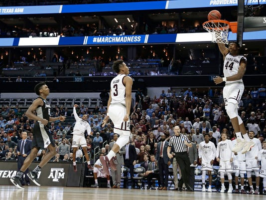 Texas A&M's Robert Williams (44) dunks against Providence as teammate Admon Gilder (3) celebrates during the second half of a first-round game in the NCAA men's college basketball tournament in Charlotte, N.C., Friday, March 16, 2018. (AP Photo/Gerry Broome)