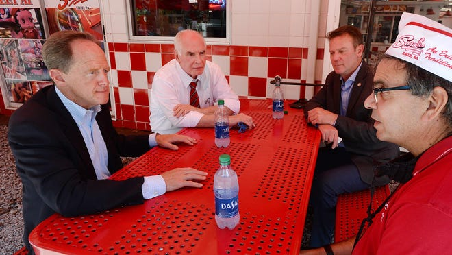 From left, U.S. Sen. Pat Toomey, R-Pa.; U.S. Rep. Mike Kelly, of Butler, R-16th Dist.; and state Sen. Dan Laughlin, of Millcreek Township, R-49th Dist., talk on Friday with Sean Candela, owner of Sara's restaurant, about Gov. Tom Wolf's decision not to move Erie County into the green phase of COVID-19 recovery.