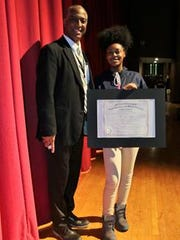 Excellence Award presented to Rejeah Cutliff from Dr. Phillip Williamson, Principal of the school.