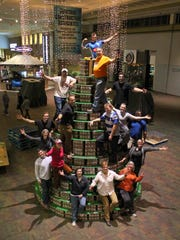 Volunteers from Asheville's men's and women's rugby teams celebrate while decorating the Ingles Giving Tree at the Asheville Mall on Monday. The Giving Tree is a 10-ton construction of non-perishable food items donated by Ingles Markets and decorated by staff and volunteers at MANNA FoodBank.