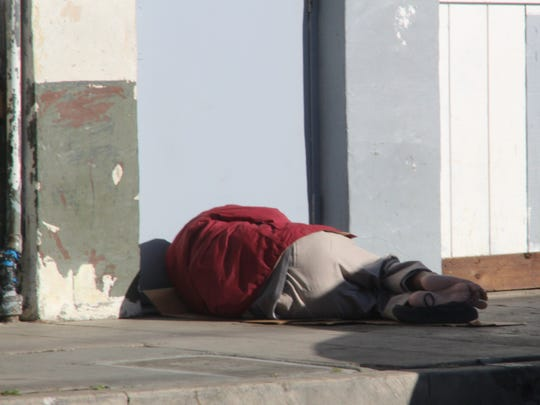 A person sleeps barefoot on Soledad Street in Chinatown Friday afternoon. Temperatures are expected to drop to freezing levels in Salinas overnight, according to the National Weather Service.