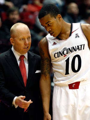 Cincinnati Bearcats head coach Mick Cronin talks with guard Troy Caupain during a stop in play in the first half.