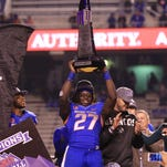 Boise State running back Jay Ajayi hoists the Mountain West championship trophy after the Broncos beat Fresno State in the title game last season.