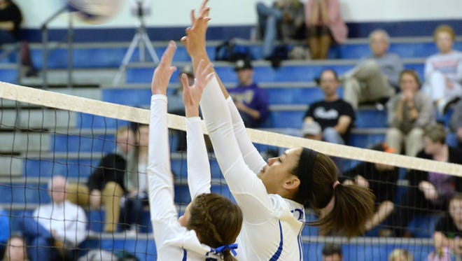 Jayden Beasley and Sara Ross (6) got up for a block during Monday's Valley District volleyball semifinals. The Indians swept TA in the match.